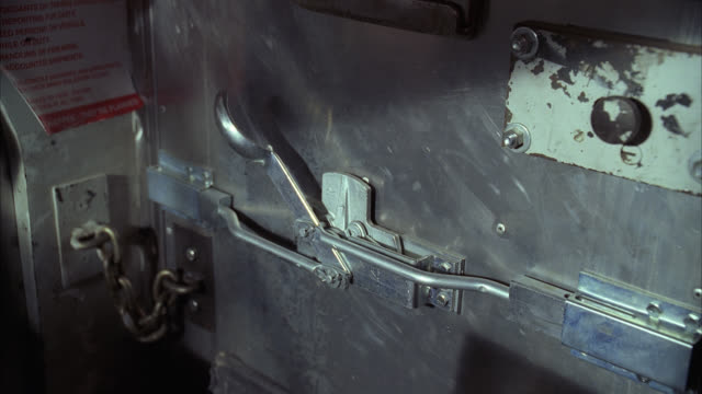 MEDIUM ANGLE OF METAL OR STEEL DOOR ON INSIDE OF TRUCK OR ARMORED TRUCK. HANDLE MOVES BACK AND FORTH. CHAIN ON DOOR. MAT WAVED IN FRONT OF DOOR. COULD BE STAND-OFF.