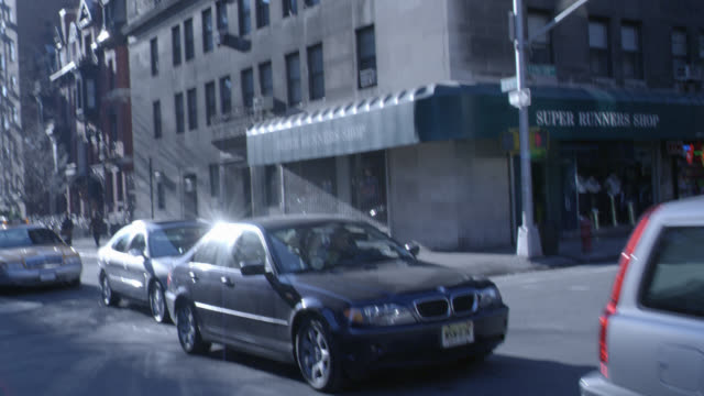 hand held angle of nyc street. cars driving, store, one way street sign, buildings. - one way stock videos & royalty-free footage