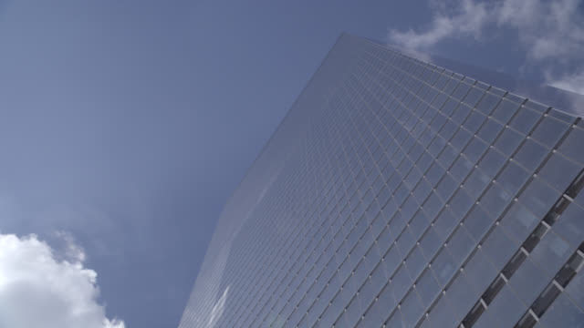 up angle of new york city office building or skyscraper. contemporary glass and steel architecture. scrolling sign, screen, or message inside lobby. - mercedes benz stock videos and b-roll footage