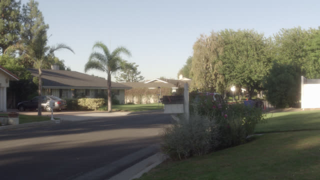 wide angle of neighborhood or suburbs. pan right to one story house or home, driveways with cars parked, and mailboxes. pan left to sun shining. could be middle class. - middle class stock videos & royalty-free footage