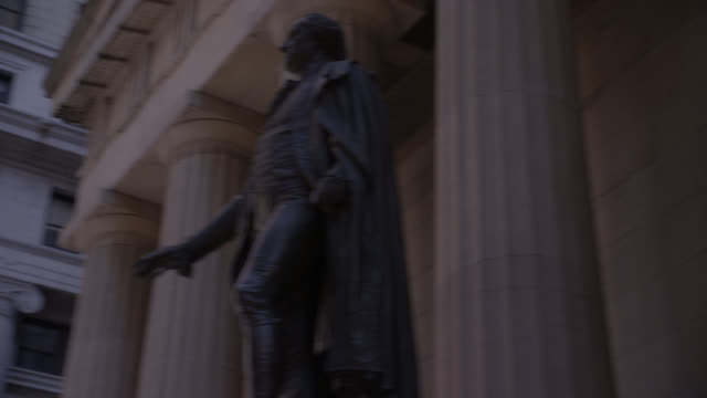 vídeos de stock e filmes b-roll de medium angle of george washington statue in front of the federal building in wall street. pov zooms out left to show american flags at the new york stock exchange. - edifício federal