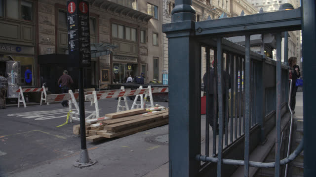 """medium angle pan left to right of """"wall street station"""" subway entrance and exit. construction visible on street at beginning of shot. men and women walk up steps to sidewalk from subway station. financial district. - 2008 stock videos & royalty-free footage"""