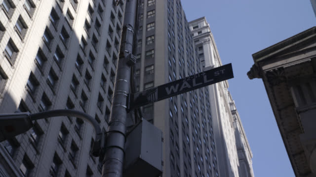 "zoom in and up of ""wall st"" street sign on lamp post. pov moves left to new york stock exchange and 100 broadway skyscrapers and then returns to sign. financial district. - 2008 stock videos & royalty-free footage"