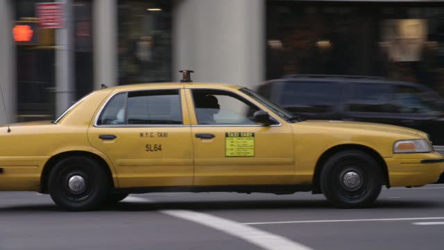 PAN LEFT TO RIGHT AS A TAXI DRIVES UP 6TH AVENUE IN MANHATTAN TRAFFIC THROUGH A SHOPPING AREA.