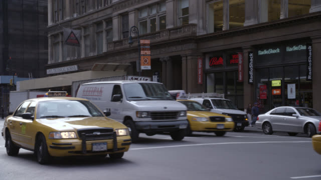 vídeos y material grabado en eventos de stock de wide angle of 6th avenue in manhattan. traffic moves through the shopping area.  a yellow taxi pulls over to the curb in front of the camera. - cement mixer