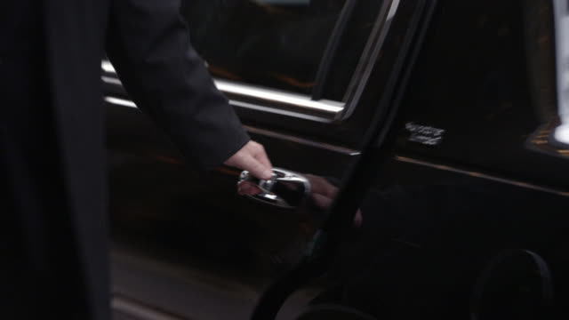 """medium angle of man and woman exiting lincoln town car in front of """"st. regis"""" hotel on madison avenue. driver opens and closes car door while doorman speaks to man and woman. upper-class, five-star hotel in midtown manhattan. - lincoln town car stock videos and b-roll footage"""