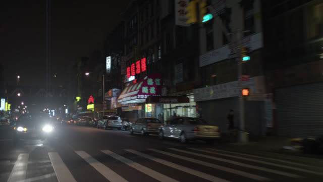 wide angle moving pov 3/4 left back of chinatown. cars with headlights pass on new york city streets and through intersection. - chinatown stock videos & royalty-free footage