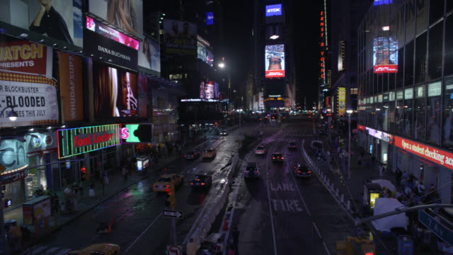 PAN DOWN OF LIMO SWERVING THROUGH CARS AND TAXIS ON NEW YORK, CITY STREETS OF TIMES SQUARE.