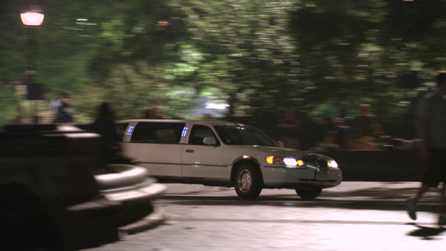 pan left to right of limo with headlights swerving around the fountain in washington square park, driving on cobblestone sidewalk, nearly colliding with people or pedestrians. greenwich village area of new york. - リムジン点の映像素材/bロール