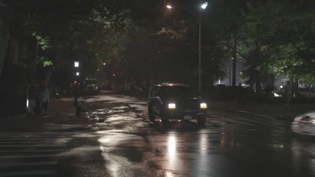 pan right to left of limo with headlights driving recklessly through intersection in greenwich village area of new york. pedestrians or onlookers watch from sidewalk near parked cars. near collisions. city street wet from rain. - limousine stock videos & royalty-free footage