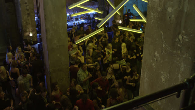 vidéos et rushes de high angle down from entrance or staircase of crowd of people dancing in nightclub or bar. drinking alcohol or cocktails.  nightlife. - discothèque