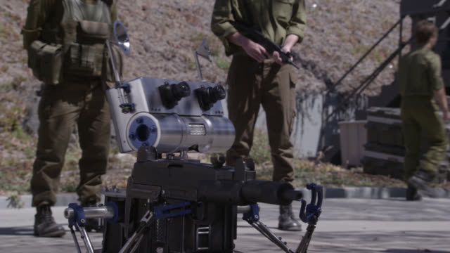 vídeos de stock, filmes e b-roll de medium angle of killer robot firing assault rifle, guarded by armed israeli soldiers. could be military base or training. gunfire. - exército