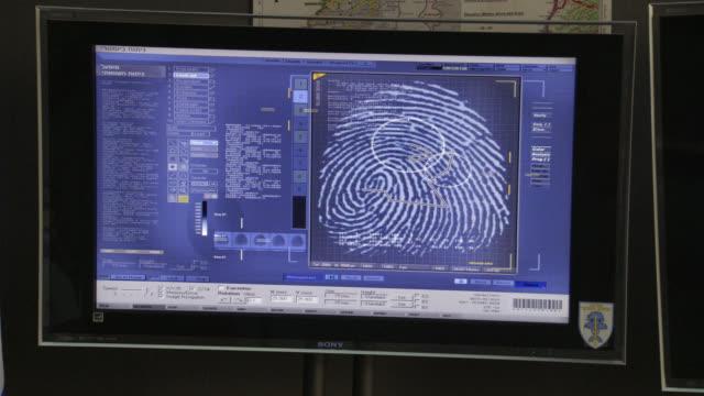 close angle of digital display on monitor or computer screen of fingerprint identification. scrolling through data. - fingerabdruck stock-videos und b-roll-filmmaterial