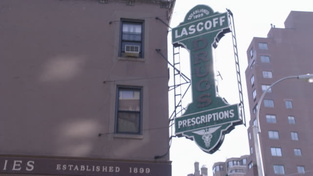 "pan down from ""lascoff drugs"" sign to pharmacy entrance with awning on the street corner of lexington avenue and 82nd street. - awning stock videos and b-roll footage"