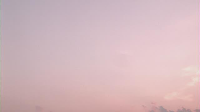 vidéos et rushes de pan left to right of pink and purple clouds against blue sky. sun rays. - ciel seulement