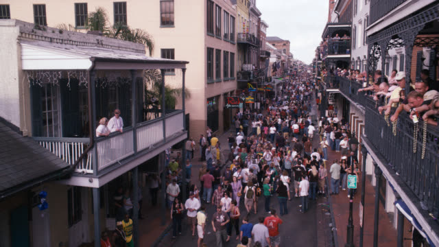 pan up of crowd of people in city street, bourbon street. celebration, party, festival, mardi gras. people throwing beads from balconies. - new orleans mardi gras stock videos and b-roll footage