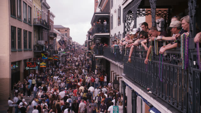 high angle down of crowd of people in city street, bourbon street. celebration, party, festival, mardi gras. people throwing beads from balconies. - bourbon street new orleans stock videos and b-roll footage