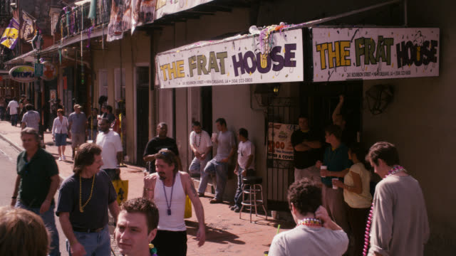 pan up from entrance and sign for the frat house, bar or nightclub. crowds or people, pedestrians, tourists on city street. bourbon street, mardi gras. - new orleans mardi gras stock videos and b-roll footage