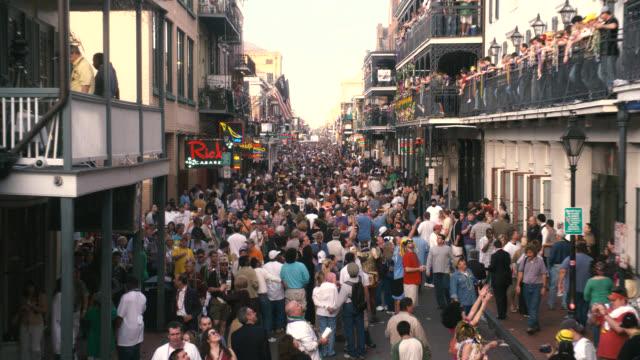 vídeos y material grabado en eventos de stock de pan right to left of crowd of people in city street, bourbon street. celebration, party, festival, mardi gras. people throwing beads from balconies. - mardi gras