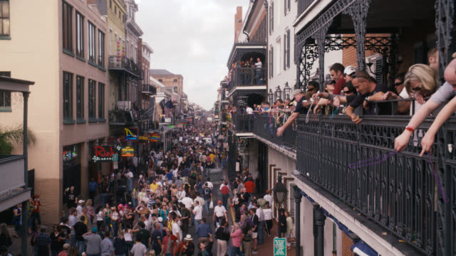 pan down of crowd of people in city street, bourbon street. celebration, party, festival, mardi gras. people throwing beads from balconies. - mardi gras stock videos and b-roll footage