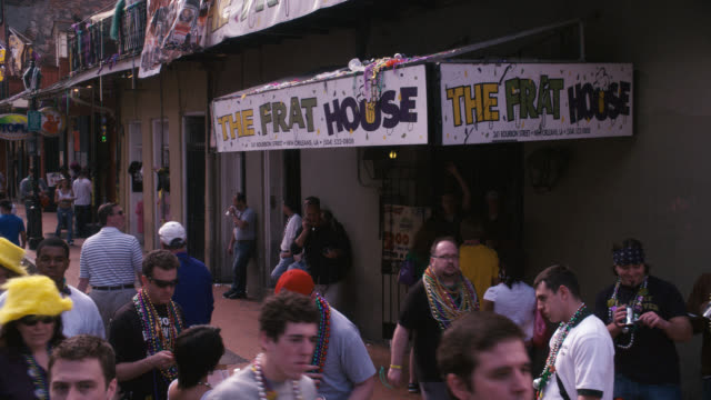 pan down to entrance and sign for the frat house, bar or nightclub. crowds or people, pedestrians, tourists on city street. bourbon street, mardi gras. - bourbon street new orleans stock videos and b-roll footage