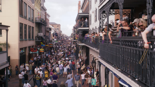 pan down of crowd of people in city street, bourbon street. celebration, party, festival, mardi gras. people throwing beads from balconies. - new orleans mardi gras stock videos and b-roll footage