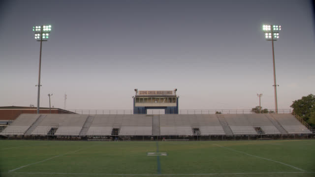 wide angle of empty football stadium and field. could be at high school. bleachers or stands in bg. - pitch stock videos & royalty-free footage