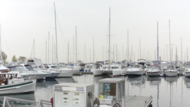 wide angle of small harbor with docked sailboats and motorboats. gasoline pump visible in fg. could be bay or lake. window edges visible as if looking out to harbor from inside. overcast day. - bay window stock videos & royalty-free footage