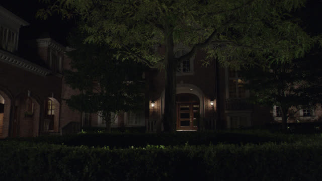 pan left to right of red brick estate or mansion entrance with cobblestone circular driveway, 4 car garage. arches, trees, lit entrance visible. - medical building stock videos and b-roll footage
