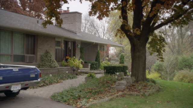 WIDE ANGLE OF SUBURBAN OR RURAL RANCH HOUSE WITH CHIMNEY AND FRONT YARD SHRUBBERY. WIND CHIMES, LARGE TREES WITH AUTUMN LEAVES VISIBLE. TRUCK PARKED BY GARAGE. OVERCAST SKY.