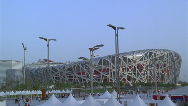 wide angle of beijing national stadium. olympic stadium. people in olympic square in fg near white tents. could be exhibit. crowds. - オリンピックスタジアム点の映像素材/bロール