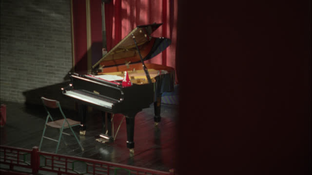 pan left to right from high angle down of piano on stage to pillar in fg.. red curtain moves in bg. metronome on piano. - playhouse stock videos & royalty-free footage