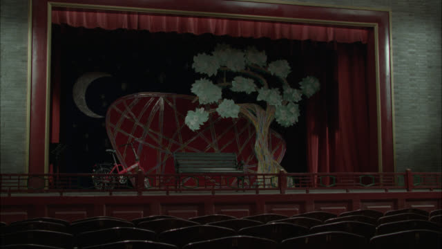 wide angle of stage in school auditorium. stage set for play. bicycle, bench, tree, and moon on stage serve as set. seats visible in fg. red curtain. could be theater or playhouse. stage light turns on. - playhouse stock videos & royalty-free footage