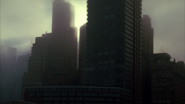 vidéos et rushes de aerial right to left of new york city on foggy day. midtown manhattan skyscrapers. sun begins to break through clouds. - brouillard