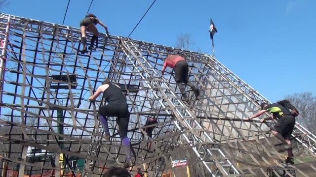 vídeos y material grabado en eventos de stock de obstacle racer on top of 20' wall climbs down - salmini