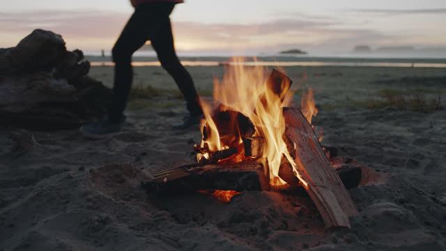 woman walks past as a campfire burns on a scenic tofino beach at sunset. - fuoco acceso video stock e b–roll