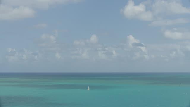 vídeos de stock, filmes e b-roll de wide shot of a lone sailing boat on the ocean - boia equipamento marítimo de segurança