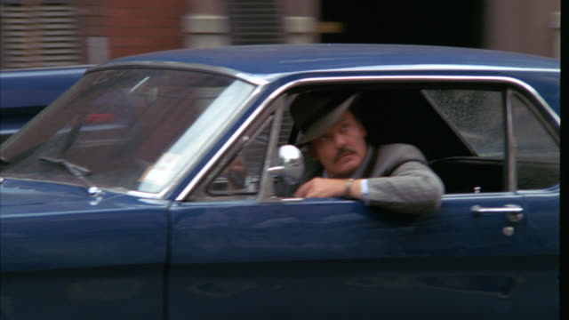 vídeos y material grabado en eventos de stock de pan up from actor stacy keach driving a 1965 ford mustang, vintage car down city street to high rise buildings, could be upper class apartment buildings or condominiums near central park. nyc streets. cities. - stacy keach