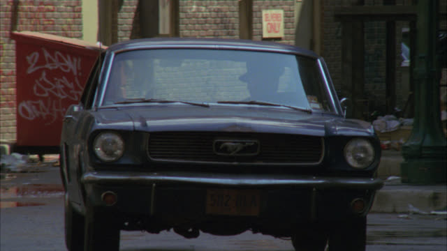 pan up from ford mustang car driving through alley littered with trash to sign for hotel. multi-story brick buildings. could be in lower class area. - ford mustang stock videos and b-roll footage