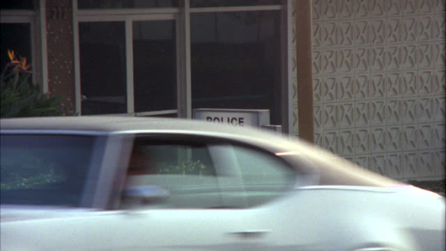 "medium angle of a sign reading ""police department"" in front of entrance to building. cars driving by in fg. police station. burbank police station. - burbank stock-videos und b-roll-filmmaterial"