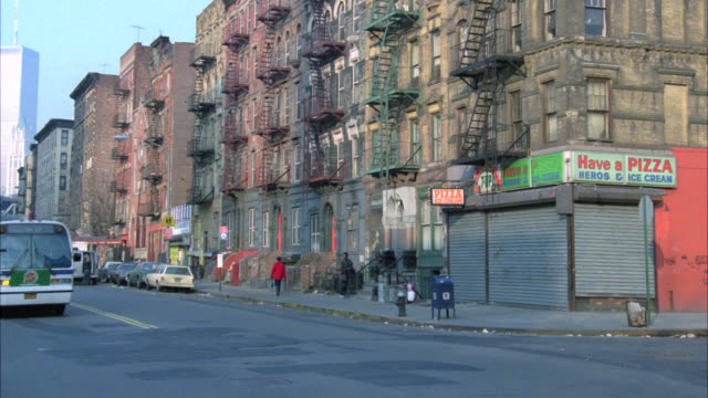 zoom in from wide angle of nyc street with world trade center or twin towers in bg to lower class brick apartment building. fire escapes. delivery truck in fg. city. could be housing projects or tenements. - slum stock-videos und b-roll-filmmaterial