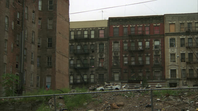 pan right to left from lower class urban area apartment buildings or tenements to rain-slick city street. could be slum. abandoned or rundown buildings. cars driving on street. pedestrians. - run down stock videos & royalty-free footage