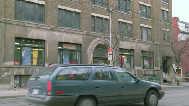 wide angle of nyc street in lower class urban area. could be school or community center. vans, city buses, and cars drive on street. pedestrians. - slum stock-videos und b-roll-filmmaterial