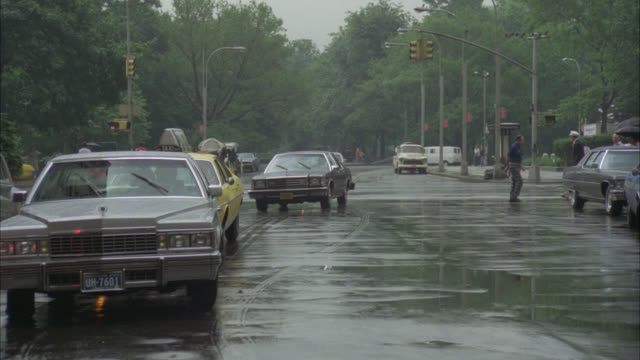 wide angle of new york city street in rain. cars and taxis pull up next to plaza hotel. fifth avenue. man in lincoln town car exits and walks towards covered entrance of hotel. awning. up angle of multi story hotel and empty flag poles. - lincoln town car stock videos and b-roll footage