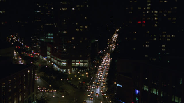 WIDE ANGLE OF TRAFFIC ON CITY STREETS AT NIGHT.