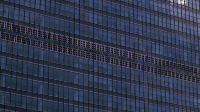 pan up of united nations building in new york city. see cloudy skies in background. see high rise office building or skyscraper with reflective glass windows. modern. - united nations stock videos & royalty-free footage