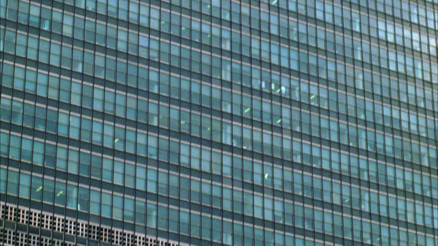 pan up of united nations headquarters building in new york city. see cloudy skies in background. see high rise office building or skyscraper with reflective glass windows. modern. - united nations building stock videos and b-roll footage