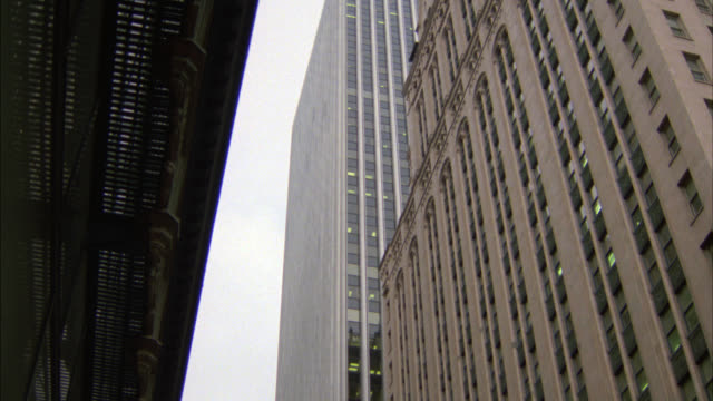 zoom in on window of skyscraper or high rise modern office building. building in fg could be hotel or another office building. could be in downtown. - fensterfront stock-videos und b-roll-filmmaterial