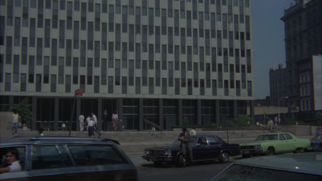 pan down office building to man sitting on hood of parked car. other man joins and they drive away on city street in fg. could be government building. high rise or skyscraper. javits federal office building. federal buildings. - federal building stock videos & royalty-free footage