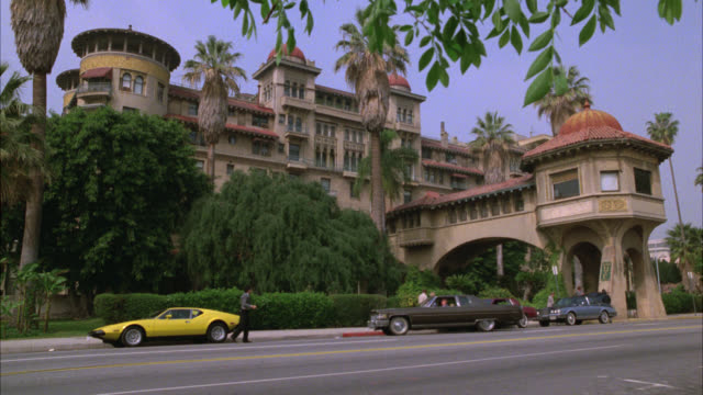 wide angle of high rise hotel with turrets. mediterranean style. hotel is really the green hotel in pasadena. landmark. palm trees in bg. car, brown cadillac drives up to curb. valet drives car away. city street in fg. - pasadena california stock videos and b-roll footage